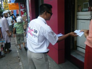 Protester Hands out Leaflet about Article 18 - Photo © MDCF