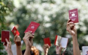 Myanmar nationals hold up their passports outside the embassy of Myanmar in Singapore